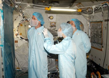 KENNEDY SPACE CENTER, FLA. - - In the Space Station Processing Facility, STS-114 Mission Specialist Stephen Robinson (left) learns about the Japanese Experiment Module (JEM) from Jennifer Goldsmith (center), with United Space Alliance at Johnson Space Center, and Louise Kleba (right), with USA at KSC. Crew members are at KSC to become familiar with Shuttle and mission equipment. The mission is Logistics Flight 1, which is scheduled to deliver supplies and equipment plus the external stowage platform to the International Space Station.