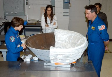 KENNEDY SPACE CENTER, FLA. - STS-114 Mission Specialists Wendy Lawrence (left) and Stephen Robinson (right) look at the insert for Discovery?s nose cap that is being fitted with thermal protection system insulation blankets. The mission crew is spending time becoming familiar with Shuttle and mission equipment. The mission is Logistics Flight 1, which is scheduled to deliver supplies and equipment plus the external stowage platform to the International Space Station.