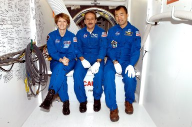 KENNEDY SPACE CENTER, FLA. - STS-114 Commander Eileen Collins and Mission Specialists Charles Camarda and Soichi Noguchi sit outside the crew hatch on the orbiter Discovery. Noguchi is with the Japanese Aerospace and Exploration Agency. They and other crew members are at KSC becoming familiar with Shuttle and mission equipment. The mission is Logistics Flight 1, which is scheduled to deliver supplies and equipment plus the external stowage platform to the International Space Station.