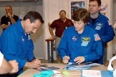 KENNEDY SPACE CENTER, FLA. - Members of the STS-114 crew sign autographs for employees in the SRB Assembly and Refurbishment Facility. From left are Mission Specialists Charles Camarda and Wendy Lawrence. In the background, at right, is Pilot James Kelly. The crew is at KSC for familiarization with Shuttle and mission equipment. The STS-114 mission is Logistics Flight 1, which is scheduled to deliver supplies and equipment, plus the external stowage platform, to the International Space Station.
