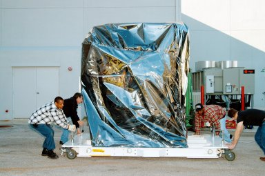 KENNEDY SPACE CENTER, FLA. - At the Astrotech Space Operations processing facilities near KSC, workers check the moveable pallet holding NASA?s MESSENGER spacecraft. MESSENGER - short for MErcury Surface, Space ENvironment, GEochemistry and Ranging - will be taken into a high bay clean room and employees of the Johns Hopkins University Applied Physics Laboratory, builders of the spacecraft, will perform an initial state-of-health check. Then processing for launch can begin, including checkout of the power systems, communications systems and control systems. The thermal blankets will also be attached for flight. MESSENGER will be launched May 11 on a six-year mission aboard a Boeing Delta II rocket. Liftoff is targeted for 2:26 a.m. EDT on Tuesday, May 11.