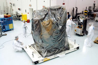 KENNEDY SPACE CENTER, FLA. - In the high bay clean room at the Astrotech Space Operations processing facilities near KSC, workers get ready to remove the protective cover from NASA?s MESSENGER spacecraft. Employees of the Johns Hopkins University Applied Physics Laboratory, builders of the spacecraft, will perform an initial state-of-health check. Then processing for launch can begin, including checkout of the power systems, communications systems and control systems. The thermal blankets will also be attached for flight. MESSENGER - short for MErcury Surface, Space ENvironment, GEochemistry and Ranging - will be launched May 11 on a six-year mission aboard a Boeing Delta II rocket. Liftoff is targeted for 2:26 a.m. EDT on Tuesday, May 11.