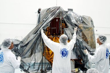KENNEDY SPACE CENTER, FLA. - In the high bay clean room at the Astrotech Space Operations processing facilities near KSC, workers remove the protective cover from NASA?s MESSENGER spacecraft. Employees of the Johns Hopkins University Applied Physics Laboratory, builders of the spacecraft, will perform an initial state-of-health check. Then processing for launch can begin, including checkout of the power systems, communications systems and control systems. The thermal blankets will also be attached for flight. MESSENGER - short for MErcury Surface, Space ENvironment, GEochemistry and Ranging - will be launched May 11 on a six-year mission aboard a Boeing Delta II rocket. Liftoff is targeted for 2:26 a.m. EDT on Tuesday, May 11.