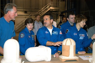 KENNEDY SPACE CENTER, FLA. - In the SRB Assembly and Refurbishment Facility, STS-114 crew members look at test designs of the bolt catcher insulation. Starting second from left are Mission Specialists Wendy Lawrence and Charles Camarda; Pilot James Kelly; and Commander Eileen Collins. The STS-114 crew is at KSC for familiarization with Shuttle and mission equipment. The mission is Logistics Flight 1, which is scheduled to deliver supplies and equipment, plus the external stowage platform, to the International Space Station.