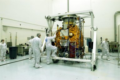 KENNEDY SPACE CENTER, FLA. -- Astrotech Space Operations facilities near KSC, workers check the Mercury Surface, Space Environment, Geochemistry and Ranging (MESSENGER) spacecraft after completing rotation on the turnover fixture. Workers will perform the propulsion system phasing test - firing gas through the thrusters in order to verify that the right thrusters fire when expected - as part of prelaunch testing at the site. Launch is scheduled for May 11 from Pad 17-B, Cape Canaveral Air Force Station. The spacecraft will fly past Venus three times and Mercury twice before starting a year-long orbital study of Mercury in July 2009.