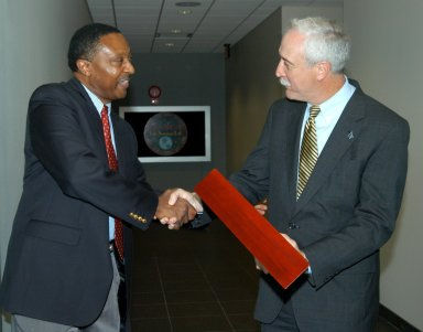 KENNEDY SPACE CENTER, FLA. -- Former astronaut Winston Scott (left) presents a NASA flag flown at the KSC Space Life Sciences Lab to NASA Administrator Sean O?Keefe. The flag was flown during construction through the dedication of the Lab. The presentation was during a tour of the Lab following the launching ceremony at the KSC Visitor Complex for the new Florida quarter issued by the U.S. Mint. The ceremony was emceed by Center Director Jim Kennedy and included remarks by O?Keefe, Florida Gov. Jeb Bush, U.S. Mint Director Henrietta Holsman Fore and Deputy Secretary of the Treasury Samuel W. Bodman. The new lab is a state-of-the-art facility built for ISS biotechnology research. It was developed as a partnership between NASA-KSC and the State of Florida.