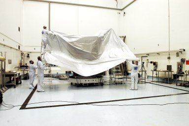 KENNEDY SPACE CENTER, FLA. - Workers at Astrotech Space Operations facilities in Titusville, Fla., finish encapsulating the MESSENGER (Mercury Surface, Space Environment, Geochemistry and Ranging) spacecraft for a move from its current location in the hazardous processing facility, where it has been since arrival March 10, to an adjacent nonhazardous payload processing facility. The remainder of its final assembly and testing will be completed there. The spacecraft will return to the hazardous processing facility when ready for fueling, spin balance testing and mating to the upper stage. MESSENGER is scheduled to launch no earlier than July 30 from Cape Canaveral Air Force Station. MESSENGER is a scientific investigation of the planet Mercury, the least explored terrestrial planet. Understanding Mercury and how it was formed is essential to understanding the other terrestrial planets and their evolution. The MESSENGER mission will orbit Mercury after making two flybys of the planet, using data collected during the flybys as an initial guide to perform a more focused scientific investigation of this mysterious world. The spacecraft will enter Mercury orbit in March 2011 and carry out comprehensive measurements for one full Earth year.
