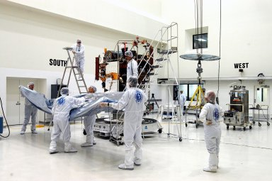 KENNEDY SPACE CENTER, FLA. - - Workers at Astrotech Space Operations in Titusville, Fla., remove the cover from the MESSENGER (Mercury Surface, Space Environment, Geochemistry and Ranging) spacecraft inside the nonhazardous payload processing facility. Final assembly and testing will be completed at this site. The spacecraft will return to the hazardous processing facility when ready for fueling, spin balance testing and mating to the upper stage. MESSENGER is scheduled to launch no earlier than July 30 from Cape Canaveral Air Force Station. MESSENGER is a scientific investigation of the planet Mercury, the least explored terrestrial planet. Understanding Mercury and how it was formed is essential to understanding the other terrestrial planets and their evolution. The MESSENGER mission will orbit Mercury after making two flybys of the planet, using data collected during the flybys as an initial guide to perform a more focused scientific investigation of this mysterious world. The spacecraft will enter Mercury orbit in March 2011 and carry out comprehensive measurements for one full Earth year.