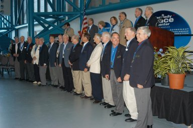KENNEDY SPACE CENTER, FLA. -- Following the induction ceremony welcoming five new space program heroes in the U.S. Astronaut Hall of Fame, the members line up for a commemorative photo. From left, in front, are John Young, John Glenn Jr., Scott Carpenter, Wally Schirra, Gordon Cooper, Walt Cunningham, Ed Mitchell, Al Worden, Rick Hauck, Ed Gibson, Owen Garriott, Vance Brand, Robert Crippen, Joe Engle, Dan Brandenstein. In back are space author Andrew Chaikin, at the podium; and Norm Thagard, June Scobee representing her late husband Dick Scobee, Kathryn Sullivan, Fred Gregory, Richard Covey and Jim Lovell. The induction ceremony was held at the Apollo/Saturn V Center at KSC. The U.S. Astronaut Hall of Fame opened in 1990 to provide a place where space travelers could be remembered for their participation and accomplishments in the U.S. space program. The five inductees join 52 previously honored astronauts from the ranks of the Gemini, Apollo, Skylab, Apollo-Soyuz, and Space Shuttle programs.