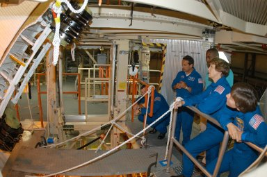 KENNEDY SPACE CENTER, FLA. -- In the Orbiter Processing Facility, STS-114 crew members look at one of the Rudder Speed Brake actuators. Seen at right are Mission Specialist Charles Camarda, Mission Commander Eileen Collins and Mission Specialist Wendy Lawrence. Crew members are touring several areas on Center. The STS-114 mission is Logistics Flight 1, which is scheduled to deliver supplies and equipment plus the external stowage platform to the International Space Station.