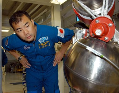KENNEDY SPACE CENTER, FLA. -- STS-114 Mission Specialist Soichi Noguchi looks closely at low pressure oxidizer duct in the Space Shuttle Main Engine Shop at KSC. He and other crew members are touring several areas on the Center. The STS-114 mission is Logistics Flight 1, which is scheduled to deliver supplies and equipment plus the external stowage platform to the International Space Station.