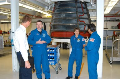 KENNEDY SPACE CENTER, FLA. -- In the Space Shuttle Main Engine Shop at KSC, Boeing Tech Operations? Team Manager Matthew McClelland (left) talks with STS-114 Pilot James Kelly. At right are Mission Specialists Wendy Lawrence and Charles Camarda. One of the main engines is in the background. Crew members are touring several areas on Center. The STS-114 mission is Logistics Flight 1, which is scheduled to deliver supplies and equipment plus the external stowage platform to the International Space Station.