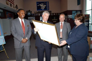 KENNEDY SPACE CENTER, FLA. - In the Space Station Processing Facility, Center Director Jim Kennedy (second from left) presents a framed photo to Mary Harney , Tanaiste (deputy prime minister) and Minister for Enterprise, Trade and Employment of Ireland. Harney is visiting KSC to support a Memorandum of Understanding between Florida Spaceport Authority and the Irish government?s training and employment authority (FAS). The joint initiative enables Irish students to work with science and engineering experts during a six-week program in Florida. At far left is FSA Director Capt. Winston Scott. Next to Harney is Paul Haran, secretary to the deputy prime minister.