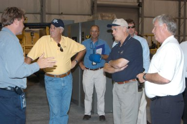 KENNEDY SPACE CENTER, FLA. - From left, Martin Wilson, manager of Thermal Protection System (TPS) operations for United Space Alliance, briefs NASA Administrator Sean O?Keefe, KSC Director of the Spaceport Services Scott Kerr, NASA Associate Administrator of the Space Operations Mission Directorate William Readdy, and Center Director James Kennedy (right) on the temporary tile shop set up in the RLV hangar. O?Keefe and Readdy are visiting KSC to survey the damage sustained by KSC facilities from Hurricane Frances. The Thermal Protection System Facility (TPSF), which creates the TPS tiles, blankets and all the internal thermal control systems for the Space Shuttles, is almost totally unserviceable at this time after losing approximately 35 percent of its roof in the storm, which blew across Central Florida Sept. 4-5. Undamaged equipment was removed from the TPSF and stored in the hangar. NASA?s three Space Shuttle orbiters -- Discovery, Atlantis and Endeavour - along with the Shuttle launch pads, all of the critical flight hardware for the orbiters and the International Space Station, and NASA?s Swift spacecraft, awaiting launch in October, were well protected and unharmed.