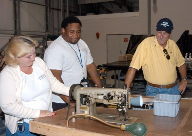 KENNEDY SPACE CENTER, FLA. - - NASA Administrator Sean O?Keefe (right) looks at equipment moved from the Thermal Protection System Facility to the RLV Hangar. At left are United Space Alliance technicians Shelly Kipp and Eric Moss. O?Keefe and NASA Associate Administrator of Space Operations Mission Directorate William Readdy are visiting KSC to survey the damage sustained by KSC facilities from Hurricane Frances. The Thermal Protection System Facility (TPSF), which creates the TPS tiles, blankets and all the internal thermal control systems for the Space Shuttles, is almost totally unserviceable at this time after losing approximately 35 percent of its roof in the storm, which blew across Central Florida Sept. 4-5. Undamaged equipment was removed from the TPSF and stored in the hangar. The Labor Day storm also caused significant damage to the Vehicle Assembly Building and Processing Control Center. Additionally, the Operations and Checkout Building, Vertical Processing Facility, Hangar AE, Hangar S and Hangar AF Small Parts Facility each received substantial damage. However, well-protected and unharmed were NASA?s three Space Shuttle orbiters - Discovery, Atlantis and Endeavour - along with the Shuttle launch pads, all of the critical flight hardware for the orbiters and the International Space Station, and NASA?s Swift spacecraft that is awaiting launch in October.