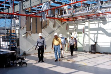 KENNEDY SPACE CENTER, FLA. - Martin Wilson (far left), manager of Thermal Protection System (TPS) operations for United Space Alliance (USA), leads NASA Administrator Sean O?Keefe (second from left) on a tour of the hurricane-ravaged Thermal Protection System Facility. The TPSF, which creates the TPS tiles, blankets and all the internal thermal control systems for the Space Shuttles, is almost totally unserviceable at this time after losing approximately 35 percent of its roof in the storm, which blew across Central Florida Sept. 4-5. Undamaged equipment was removed from the TPSF and stored in the RLV hangar. O?Keefe and NASA Associate Administrator of Space Operations Mission Directorate William Readdy are visiting KSC to survey the damage sustained by KSC facilities from the hurricane. The Labor Day storm also caused significant damage to the Vehicle Assembly Building and Processing Control Center. Additionally, the Operations and Checkout Building, Vertical Processing Facility, Hangar AE, Hangar S and Hangar AF Small Parts Facility each received substantial damage. However, well-protected and unharmed were NASA?s three Space Shuttle orbiters - Discovery, Atlantis and Endeavour - along with the Shuttle launch pads, all of the critical flight hardware for the orbiters and the International Space Station, and NASA?s Swift spacecraft that is awaiting launch in October.