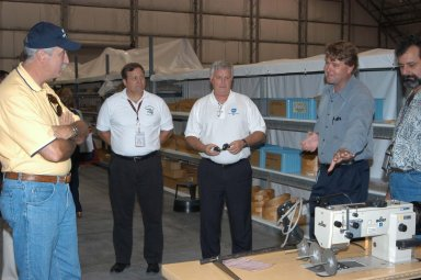 KENNEDY SPACE CENTER, FLA. - Martin Wilson (second from right), manager of Thermal Protection System (TPS) operations for United Space Alliance (USA), briefs NASA Administrator Sean O?Keefe, KSC Director of Shuttle Processing Michael E. Wetmore and Center Director James Kennedy about the temporary tile shop set up in the RLV hangar. At far right is USA Manager of Soft Goods Production in the TPSF, Kevin Harrington. O?Keefe and NASA Associate Administrator of Space Operations Mission Directorate William Readdy are visiting KSC to survey the damage sustained by KSC facilities from Hurricane Frances. The Thermal Protection System Facility (TPSF), which creates the TPS tiles, blankets and all the internal thermal control systems for the Space Shuttles, is almost totally unserviceable at this time after losing approximately 35 percent of its roof in the storm, which blew across Central Florida Sept. 4-5. Undamaged equipment was removed from the TPSF and stored in the hangar. The Labor Day storm also caused significant damage to the Vehicle Assembly Building and Processing Control Center. Additionally, the Operations and Checkout Building, Vertical Processing Facility, Hangar AE, Hangar S and Hangar AF Small Parts Facility each received substantial damage. However, well-protected and unharmed were NASA?s three Space Shuttle orbiters -- Discovery, Atlantis and Endeavour - along with the Shuttle launch pads, all of the critical flight hardware for the orbiters and the International Space Station, and NASA?s Swift spacecraft that is awaiting launch in October.