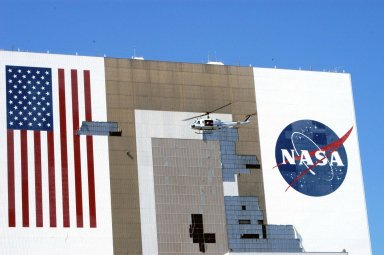 KENNEDY SPACE CENTER, FLA. - The helicopter carrying NASA Administrator Sean O?Keefe and KSC Director of Spaceport Services Scott Kerr passes by the Vehicle Assembly Building (VAB) to observe the damage inflicted by Hurricane Frances over the Labor Day weekend. The VAB lost approximately 850 tiles on the south wall, seen here. O?Keefe and NASA Associate Administrator of Space Operations Mission Directorate William Readdy are visiting KSC to survey the damage sustained by KSC facilities from the hurricane. The storm also caused significant damage to the Thermal Protection System Facility and Processing Control Center. Additionally, the Operations and Checkout Building, Vertical Processing Facility, Hangar AE, Hangar S and Hangar AF Small Parts Facility each received substantial damage. However, well-protected and unharmed were NASA?s three Space Shuttle orbiters -- Discovery, Atlantis and Endeavour - along with the Shuttle launch pads, all of the critical flight hardware for the orbiters and the International Space Station, and NASA?s Swift spacecraft that is awaiting launch in October.