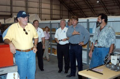 KENNEDY SPACE CENTER, FLA. - Martin Wilson (second from right), manager of Thermal Protection System (TPS) operations for United Space Alliance (USA) , introduces Kevin Harrington, manager of Soft Goods Production in the TPSF, during a briefing to (from left) NASA Administrator Sean O?Keefe, KSC Director of Shuttle Processing Michael E. Wetmore, Center Director James Kennedy and KSC Director of the Spaceport Services Scott Kerr (behind Kennedy), on the temporary tile shop set up in the RLV hangar. O?Keefe and NASA Associate Administrator of Space Operations Mission Directorate William Readdy are visiting KSC to survey the damage sustained by KSC facilities from Hurricane Frances. The Thermal Protection System Facility (TPSF), which creates the TPS tiles, blankets and all the internal thermal control systems for the Space Shuttles, is almost totally unserviceable at this time after losing approximately 35 percent of its roof in the storm, which blew across Central Florida Sept. 4-5. The Labor Day storm also caused significant damage to the Vehicle Assembly Building and Processing Control Center. Additionally, the Operations and Checkout Building, Vertical Processing Facility, Hangar AE, Hangar S and Hangar AF Small Parts Facility each received substantial damage. Undamaged equipment was removed from the TPSF and stored in the hangar. However, well-protected and unharmed were NASA?s three Space Shuttle orbiters -- Discovery, Atlantis and Endeavour - along with the Shuttle launch pads, all of the critical flight hardware for the orbiters and the International Space Station, and NASA?s Swift spacecraft that is awaiting launch in October.