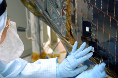 KENNEDY SPACE CENTER, FLA. - In the clean room at NASA?s Hangar AE on Cape Canaveral Air Force Station (CCAFS), a Spectrolab technician, Anna Herrera, places a new solar cell on the Swift spacecraft?s solar array. Swift is a first-of-its-kind, multi-wavelength observatory dedicated to the study of gamma-ray burst (GRB) science. Its three instruments will work together to observe GRBs and afterglows in the gamma-ray, X-ray, ultraviolet and optical wavebands. The main mission objectives for Swift are to determine the origin of gamma-ray bursts, classify gamma-ray bursts and search for new types, determine how the blast wave evolves and interacts with the surroundings, use gamma-ray bursts to study the early universe and perform the first sensitive hard X-ray survey of the sky. Swift is scheduled to launch Oct. 26 from Launch Pad 17-A, CCAFS, on a Boeing Delta 7320 rocket.