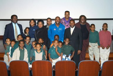 KENNEDY SPACE CENTER, FLA. - At University Community Academy in Atlanta, a NASA Explorer School, KSC Deputy Director Dr. Woodrow Whitlow Jr. (fourth from right) and astronaut Leland Melvin (fifth from right) stand for a group photo with students and staff members. At far left is Jim Harris, principal of the school. Dr. Whitlow was visiting the school to share the vision for space exploration with the next generation of explorers. Whitlow talked with students about our destiny as explorers, NASA?s stepping stone approach to exploring Earth, the Moon, Mars and beyond, how space impacts our lives, and how people and machines rely on each other in space. Also on the tour, Melvin talked about the importance of teamwork and what it takes for mission success.