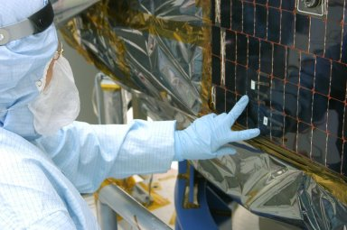 KENNEDY SPACE CENTER, FLA. - In the clean room at NASA?s Hangar AE on Cape Canaveral Air Force Station (CCAFS), a Spectrolab technician, Anna Herrera, points to the two new solar cells removed and replaced on the Swift spacecraft?s solar array. Swift is a first-of-its-kind, multi-wavelength observatory dedicated to the study of gamma-ray burst (GRB) science. Its three instruments will work together to observe GRBs and afterglows in the gamma-ray, X-ray, ultraviolet and optical wavebands. The main mission objectives for Swift are to determine the origin of gamma-ray bursts, classify gamma-ray bursts and search for new types, determine how the blast wave evolves and interacts with the surroundings, use gamma-ray bursts to study the early universe and perform the first sensitive hard X-ray survey of the sky. Swift is scheduled to launch Oct. 26 from Launch Pad 17-A, CCAFS, on a Boeing Delta 7320 rocket.