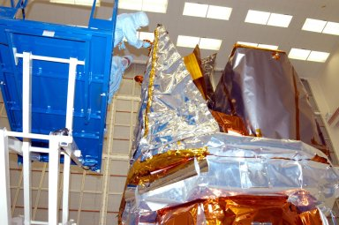 KENNEDY SPACE CENTER, FLA. - In Hangar AE at Cape Canaveral Air Force Station, technicians perform blanket closeouts on the Swift spacecraft. The blankets provide thermal stability during the mission. Swift is a first-of-its-kind multi-wavelength observatory dedicated to the study of gamma-ray burst (GRB) science. Its three instruments will work together to observe GRBs and afterglows in the gamma ray, X-ray, ultraviolet and optical wavebands. The most comprehensive study of GRB afterglows to date, Swift is expected to observe more than 200 gamma-ray bursts during its 2-year mission.