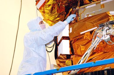 KENNEDY SPACE CENTER, FLA. - At Hangar AE, Cape Canaveral Air Force Station, a technician works on a blanket installed around the Swift spacecraft. The blankets provide thermal stability during the mission. Swift is a first-of-its-kind multi-wavelength observatory dedicated to the study of gamma-ray burst (GRB) science. Its three instruments will work together to observe GRBs and afterglows in the gamma ray, X-ray, ultraviolet and optical wavebands. Swift is expected to observe more than 200 gamma-ray bursts - the most comprehensive study of GRB afterglows to date - during its 2-year mission.