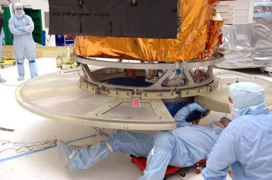 KENNEDY SPACE CENTER, FLA. - At NASA?s Hangar AE on Cape Canaveral Air Force Station (CCAFS), Fla., technicians check the attachment of the base petals of a transportation canister around the bottom of the payload attach fitting on the Swift spacecraft. Swift is a first-of-its-kind multi-wavelength observatory dedicated to the study of gamma-ray burst (GRB) science. Its three instruments will work together to observe GRBs and afterglows in the gamma ray, X-ray, ultraviolet and optical wavebands. Swift is expected to observe more than 200 gamma-ray bursts - the most comprehensive study of GRB afterglows to date - during its 2-year mission. Swift is scheduled to launch in mid-November from Launch Pad 17-A at CCAFS.