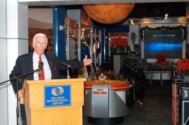 KENNEDY SPACE CENTER, FLA. - Apollo 17 Commander Gene Cernan talks about some of the exhibits in the new Kennedy Space Center Store at Orlando International Airport. NASA?s Kennedy Space Center Director Jim Kennedy and Cernan participated in the grand opening ceremony. The store will help educate millions of airport visitors about America?s space program and the Vision for Space Exploration. The store is operated by Kennedy Space Center Visitor Complex concessionaire Delaware North Parks and Resorts.
