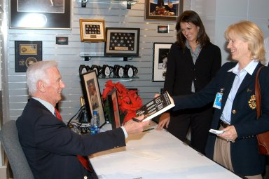 KENNEDY SPACE CENTER, FLA. - Apollo 17 Commander Gene Cernan autographs his book for attendees at the grand opening ceremony of new Kennedy Space Center Store at Orlando International Airport. NASA?s Kennedy Space Center Director Jim Kennedy and Cernan participated in the grand opening ceremony. The store will help educate millions of airport visitors about America?s space program and the Vision for Space Exploration. The store is operated by Kennedy Space Center Visitor Complex concessionaire Delaware North Parks and Resorts.