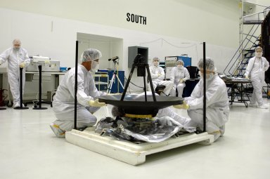 KENNEDY SPACE CENTER, FLA. - Ball Aerospace technicians at Astrotech in Titusville, Fla., begin lifting the high-gain communications antenna to attach it to an overhead crane. The antenna will be installed on the Deep Impact spacecraft. A NASA Discovery mission, Deep Impact will probe beneath the surface of Comet Tempel 1 on July 4, 2005, when the comet is 83 million miles from Earth, and reveal the secrets of its interior. During the encounter phase, the high-gain antenna transmits near-real-time images of the impact back to Earth. The spacecraft is scheduled to launch Jan. 8 aboard a Boeing Delta II rocket from Launch Complex 17-B at Cape Canaveral Air Force Station, Fla.
