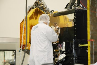 KENNEDY SPACE CENTER, FLA. - Ball Aerospace technicians prepare the Deep Impact flyby spacecraft for installation of the flight battery at Astrotech Space Operations in Titusville, Fla. About the size of a Ford Explorer, the flyby spacecraft is three-axis stabilized and uses a fixed solar array and a small NiH2 battery for its power system. A NASA Discovery mission, Deep Impact will probe beneath the surface of Comet Tempel 1 on July 4, 2005, when the comet is 83 million miles from Earth. During the encounter phase when the comet collides with the impactor projectile propelled into its path, the spacecraft?s high-gain antenna will transmit near-real-time images of the impact back to Earth. The spacecraft is scheduled to launch Jan. 8 aboard a Boeing Delta II rocket from Launch Complex 17-B at Cape Canaveral Air Force Station, Fla.