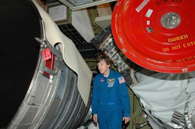 KENNEDY SPACE CENTER, FLA. - On a visit to Kennedy, STS-114 Mission Specialist Wendy Lawrence looks at an area of an engine on the orbiter Discovery. The main engines were recently installed. The designated vehicle for the mission, Discovery is in the Orbiter Processing Facility for launch processing. Discovery is scheduled for a launch planning window of May 12 to June 3, 2005.