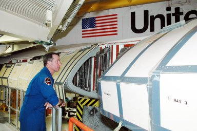 KENNEDY SPACE CENTER, FLA. - On a visit to Kennedy, STS-114 Mission Specialist Stephen Robinson looks inside the wing of the orbiter Discovery, which is in the Orbiter Processing Facility for launch processing. Discovery is scheduled for a launch planning window of May 12 to June 3, 2005.