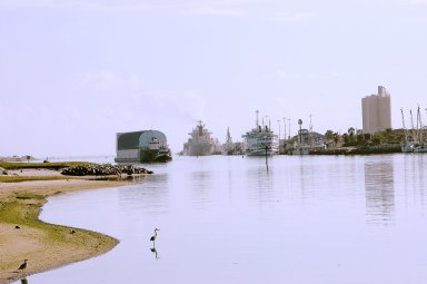 KENNEDY SPACE CENTER, FLA. - The barge carrying the newly redesigned External Tank, designated for use on Return to Flight mission STS-114, passes cruise ships as it enters Port Canaveral, Fla. The barge arrived after an approximately 900-mile journey at sea from the Michoud Assembly Facility in New Orleans. It left the facility Dec. 31 on the Pegasus, NASA?s specially designed barge, towed by Solid Rocket Booster retrieval ship Liberty Star. At Port Canaveral, the barge was then hooked up to the tugs for the last part of the journey to the Launch Complex 39 Area Turn Basin at Kennedy. Next, the External Tank will be off-loaded from the barge and transported to the Vehicle Assembly Building for its final checkout and mating to the twin Solid Rocket Boosters and orbiter Discovery. NASA and Lockheed Martin Corp. spent nearly two years modifying the 15-story, bronze-colored tank to make it safer for liftoff. Among dozens of changes is a redesigned forward bipod fitting -- a design that meets the recommendation of the Columbia Accident Investigation Board to reduce the risk to the Space Shuttle from falling debris during ascent. STS-114 is targeted for a launch opportunity beginning in May. The seven-member Discovery crew will fly to the International Space Station primarily to test and evaluate new procedures for flight safety, including Space Shuttle inspection and repair techniques.