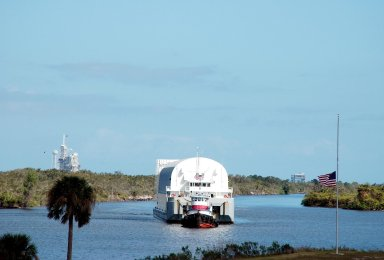 KENNEDY SPACE CENTER, FLA. - The newly redesigned External Tank, designated for use on Return to Flight mission STS-114, moves slowly toward its destination, the dock at the Launch Complex 39 Area Turn Basin, propelled by two tugboats. At left in the background is Launch Pad 39A. The External Tank arrived safely early this morning at Port Canaveral, Fla., after an approximately 900-mile journey at sea. It departed from the Michoud Assembly Facility in New Orleans Dec. 31 and was transported on the Pegasus, NASA?s specially designed barge, pulled by Solid Rocket Booster retrieval ship Liberty Star. At the port, the barge was then hooked up to the tugs for the last part of the journey to the Turn Basin. Next, the External Tank will be off-loaded from the barge and transported to the Vehicle Assembly Building for its final checkout and mating to the twin Solid Rocket Boosters and orbiter Discovery. NASA and Lockheed Martin Corp. spent nearly two years modifying the 15-story, bronze-colored tank to make it safer for liftoff. Among dozens of changes is a redesigned forward bipod fitting -- a design that meets the recommendation of the Columbia Accident Investigation Board to reduce the risk to the Space Shuttle from falling debris during ascent. STS-114 is targeted for a launch opportunity beginning in May. The seven-member Discovery crew will fly to the International Space Station primarily to test and evaluate new procedures for flight safety, including Space Shuttle inspection and repair techniques.
