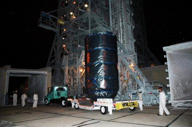 KENNEDY SPACE CENTER, FLA. - The Deep Impact spacecraft arrives before dawn at the mobile service tower on Launch Pad 17-B at Cape Canaveral Air Force Station, Fla. The spacecraft will be attached to the second stage of the Boeing Delta II rocket. Next the fairing will be installed around the spacecraft. The fairing is a molded structure that fits flush with the outside surface of the Delta II upper stage booster and forms an aerodynamically smooth joint, protecting the spacecraft during launch and ascent. Scheduled for liftoff Jan. 12, Deep Impact will probe beneath the surface of Comet Tempel 1 on July 4, 2005, when the comet is 83 million miles from Earth. After releasing a 3- by 3-foot projectile to crash onto the surface, Deep Impact?s flyby spacecraft will reveal the secrets of its interior by collecting pictures and data of how the crater forms, measuring the crater?s depth and diameter as well as the composition of the interior of the crater and any material thrown out, and determining the changes in natural outgassing produced by the impact. It will send the data back to Earth through the antennas of the Deep Space Network. Deep Impact is a NASA Discovery mission.