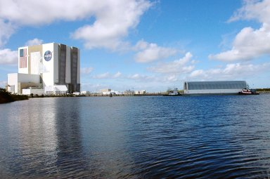 KENNEDY SPACE CENTER, FLA. - The barge carrying the newly redesigned External Tank, designated for use on Return to Flight mission STS-114, is towed toward the Launch Complex 39 Area Turn Basin at Kennedy. At left is the Vehicle Assembly Building. The barge arrived after an approximately 900-mile journey at sea from the Michoud Assembly Facility in New Orleans. It left the facility Dec. 31 on the Pegasus, NASA?s specially designed barge, towed by Solid Rocket Booster retrieval ship Liberty Star. At Port Canaveral, the barge was then hooked up to the tugs for the last part of the journey. Next, the External Tank will be off-loaded from the barge and transported to the Vehicle Assembly Building for its final checkout and mating to the twin Solid Rocket Boosters and orbiter Discovery. NASA and Lockheed Martin Corp. spent nearly two years modifying the 15-story, bronze-colored tank to make it safer for liftoff. Among dozens of changes is a redesigned forward bipod fitting -- a design that meets the recommendation of the Columbia Accident Investigation Board to reduce the risk to the Space Shuttle from falling debris during ascent. STS-114 is targeted for a launch opportunity beginning in May. The seven-member Discovery crew will fly to the International Space Station primarily to test and evaluate new procedures for flight safety, including Space Shuttle inspection and repair techniques.