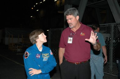 KENNEDY SPACE CENTER, FLA. - STS-114 Mission Specialist Wendy Lawrence listens to Space Shuttle Program Manager Bill Parsons while they are in the Vehicle Assembly Building observing the newly redesigned External Tank being lifted to a ?checkout cell? where the tank?s mechanical, electrical and thermal protection systems are inspected. Crew members are at Kennedy to observe tank activities. The tank will also undergo new processes resulting from its redesign, including inspection of the bipod heater and External Tank separation camera. The tank is designated to fly on Shuttle Discovery on Return to Flight mission STS-114. The launch window is May 12 to June 3, 2005.