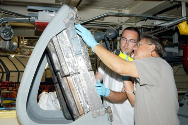 KENNEDY SPACE CENTER, FLA. -In the Orbiter Processing Facility, Matt Scott (left), with United Space Alliance, and Donald Wall (right), with NASA Quality Assurance, closely inspect the final Reinforced Carbon-Carbon (RCC) panel to be installed on orbiter Discovery?s left wing. The leading edges of each of an orbiter?s wings have 22 RCC panels. They are light gray and made entirely of carbon composite material, which protect the orbiter during re-entry. The molded components are approximately 0.25- to 0.5-inch thick and capable of withstanding temperatures up to 3,220 degrees F. Following the Columbia accident in February 2002, which was caused by a breach in an RCC panel that allowed hot gases into the vehicle, each panel on Discovery was removed and thoroughly inspected before final reinstallation. Discovery is the designated orbiter to fly on the Return to Flight mission STS-114, the first Space Shuttle to launch since the accident. The launch window for the mission is May 12 to June 3, 2005.