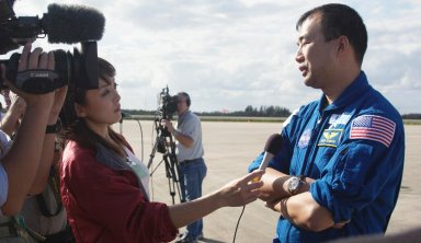KENNEDY SPACE CENTER, FLA. - At the Shuttle Landing Facility, STS-114 Mission Specialist Soichi Noguchi talks to a reporter before he and the rest of the crew depart Kennedy Space Center. Noguchi is with the Japanese Space Agency. The crew was at KSC to observe the newly redesigned External Tank and new 50-foot-long Orbiter Boom Sensor System (OBSS). Among redesign changes on the ET is the forward bipod fitting to reduce the risk to the Shuttle from falling debris during ascent. A camera has also been added to capture separation of the ET from the Shuttle after launch. The OBSS attaches to the end of the Shuttle?s robotic arm and equips the orbiter with cameras and laser systems to inspect the Shuttle?s Thermal Protection System while in space. The launch window for Return to Flight mission STS-114 is May 12 to June 3, 2005. (Photo: Michael R. Brown)