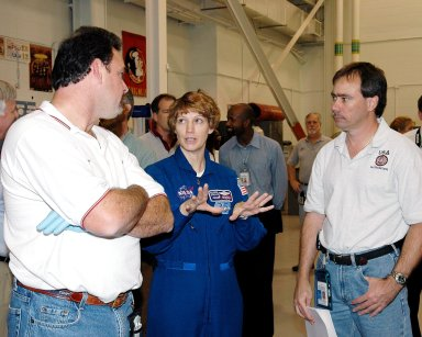 KENNEDY SPACE CENTER, FLA. - In the Remote Manipulator Lab inside the Vehicle Assembly Building, STS-114 Mission Commander Eileen Collins talks with United Space Alliance engineers about the 50-foot-long Orbiter Boom Sensor System (OBSS) that will fly on Shuttle Discovery on Return to Flight mission STS-114. The OBSS attaches to the end of the Shuttle?s robotic arm. The system is one of the new safety measures for Return to Flight, equipping the orbiter with cameras and laser systems to inspect the Shuttle?s Thermal Protection System while in space. The mission launch window is May 12 to June 3, 2005.