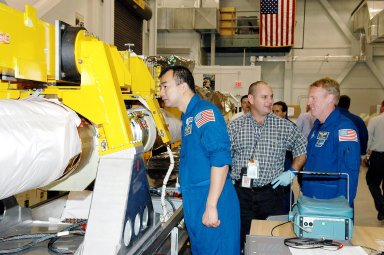 KENNEDY SPACE CENTER, FLA. - In the Remote Manipulator Lab inside the Vehicle Assembly Building, STS-114 Mission Specialists Soichi Noguchi (left) and Andrew Thomas (far right) get a close look at about the 50-foot-long Orbiter Boom Sensor System (OBSS) that will fly on Shuttle Discovery on Return to Flight mission STS-114. Between them is Rafael Rodriguez, an advanced systems technician with United Space Alliance. The OBSS attaches to the end of the Shuttle?s robotic arm. The system is one of the new safety measures for Return to Flight, equipping the orbiter with cameras and laser systems to inspect the Shuttle?s Thermal Protection System while in space. The mission launch window is May 12 to June 3, 2005.