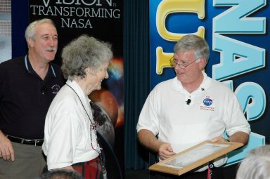 KENNEDY SPACE CENTER, FLA. - After the NASA Update by Administrator Sean O?Keefe (left), Center Director Jim Kennedy (right) presented a One NASA Peer Award to Virginia Whitehead for her outstanding customer service. Whitehead is a manager in the Center?s Payload Processing Directorate. The award is given to recognize employees who have demonstrated behaviors consistent with the spirit of One NASA and are called Peer Awards because candidates must be nominated by their peers.