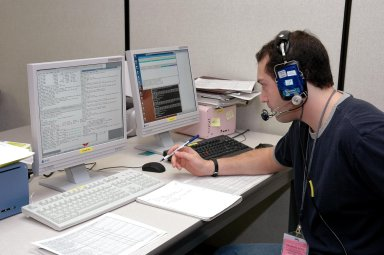 KENNEDY SPACE CENTER, FLA. - An employee at the Space Station Processing Facility monitors engineering certification testing of the Alpha Magnetic spectrometer (AMS). The AMS is a superconducting magnet that will be used in an experiment from the International Space Station (ISS) to search for antimatter and dark matter in space. The testing is being performed to ensure that data flow from the external payload AMS and the internal AMS crew operation post can be successfully routed through the ISS systems.