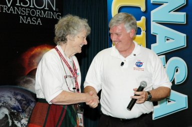 KENNEDY SPACE CENTER, FLA. - Center Director Jim Kennedy (right) congratulates Virginia Whitehead upon her receipt of a One NASA Peer Award. The award recognizes Whitehead for her outstanding customer service. Whitehead is a manager in the Center?s Payload Processing Directorate. The award was presented in the Press Site Auditorium following the NASA Update by NASA Administrator Sean O'Keefe. The award is given to recognize employees who have demonstrated behaviors consistent with the spirit of One NASA and are called Peer Awards because candidates must be nominated by their peers.