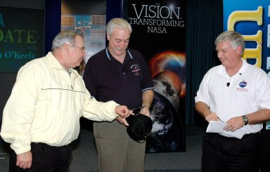 KENNEDY SPACE CENTER, FLA. - NASA Administrator Sean O?Keefe (center) is presented with a Deep Impact hat in the Press Site Auditorium following his report to employees on the state of the Agency. He is accompanied on stage by Center Director Jim Kennedy (right). The update was broadcast live via NASA Television. O'Keefe focused on the achievements of 2004 and the goals set for 2005. His remarks emphasized the milestones met in NASA's Vision for Space Exploration, including the launch of the comet-chasing Deep Impact mission and the landing of the Huygens probe on Jupiter?s moon Titan, both occurring in the past two days, and the progress made in meeting the requirements to return the Space Shuttle to flight. O?Keefe?s briefing included a dialogue with Associate Administrator of NASA?s Office of Exploration Systems Craig Steidle and Center Director Jim Kennedy, live; and Manager of the Space Station Office Bill Gerstenmaier and Director of Advanced Planning and Jet Propulsion Laboratory Charles Elachi, via satellite.