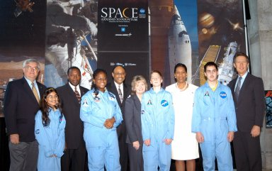 KENNEDY SPACE CENTER, FLA. - Students from one of NASA?s Explorer Schools, Stewart Middle School in Tampa pose for a photo with other guests visiting the Museum of Science and Industry (MOSI) in Tampa. At left, in the back row, are former astronaut Dan Brandenstein, current vice president of Consolidated Space Operations Centers (CSOC), and KSC Deputy Director Dr. Woodrow Whitlow Jr. In the center is Ronte Smith, southeast regional sales manager for General Motors, and Gail Rymer, with Lockheed Martin. On the right are Dr. Adena Williams Loston, chief education officer at NASA Headquarters, and Wit Ostrenko, president of MOSI. The MOSI is featuring the space exhibits Space: A Journey to Our Future, an extraordinary, interactive exhibition designed to entertain, educate and inspire; and SPACE STATION, the first cinematic journey to the International Space Station (ISS), where audiences can experience for themselves life in zero gravity aboard the new station.