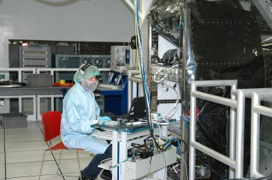 KENNEDY SPACE CENTER, FLA. - An employee at the Space Station Processing Facility performs engineering certification testing of the Alpha Magnetic spectrometer (AMS). The AMS is a superconducting magnet that will be used in an experiment from the International Space Station (ISS) to search for antimatter and dark matter in space. The testing is being performed to ensure that data flow from the external payload AMS and the internal AMS crew operation post can be successfully routed through the ISS systems.
